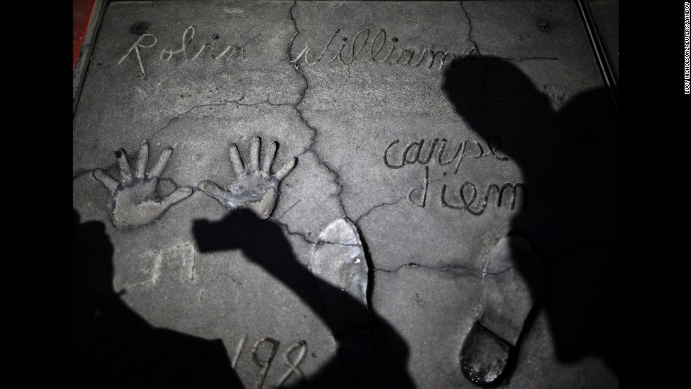 "<strong>August 12:</strong> Following the death of actor Robin Williams, people photograph his handprints and footprints at TCL Chinese Theater in Los Angeles. Williams, <a href=""http://www.cnn.com/2014/08/11/showbiz/gallery/robin-williams/index.html"">a brilliant shapeshifter</a> who could channel his frenetic energy into delightful comic characters like ""Mrs. Doubtfire"" or harness it into richly nuanced work like his Oscar-winning turn in ""Good Will Hunting,"" <a href=""http://www.cnn.com/2014/08/14/showbiz/robin-williams-parkinsons-disease/index.html"">committed suicide</a> at his home in the San Francisco Bay Area. He was 63."