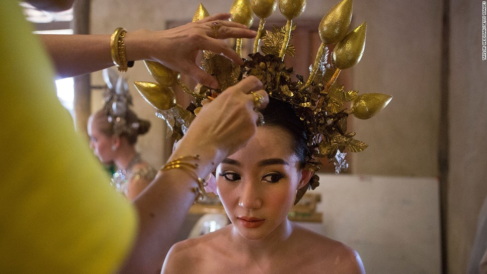 "DECEMBER 4 - CHIANG MAI, THAILAND: A Thai women prepares for a parade and ceremony in honor of King Bhumibol Adulyadej's birthday. <a href=""http://cnn.com/2014/10/06/world/asia/thailand-king-bhumibol-gallbladder/"">The world's longest-reigning monarch</a> is a deeply revered figure in Thailand, where his portrait hangs in government offices and many homes."