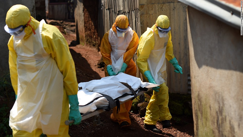 "Health workers from Sierra Leone's Red Cross Society Burial Team carry a corpse out of a house. ""We receive very positive feedback from the communities,"" James said. ""We have had zero cases of infection of our burial team members, which really goes to show the standards of our protocols and how strictly the teams follow the dressing and undressing rules. Most importantly, the teams abide by the practices of no touch and avoiding crowded spaces. We do continuous training with our burial teams so that they remain alert. Although cases levels are going down, we cannot become complacent."""