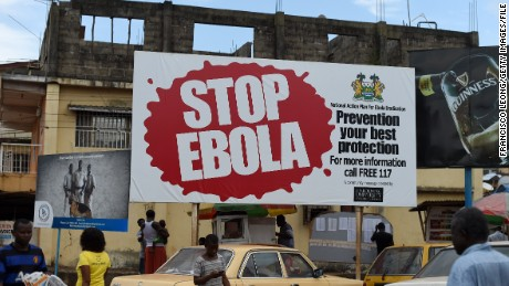 People walk past a billboard with a message about ebola in Freetown, on November 7, 2014. West Africa's regional bloc on November 7 called for international help to go beyond immediate medical care for Ebola-hit nations, warning that lives had been blighted by the epidemic. AFP PHOTO/ FRANCISCO LEONG (Photo credit should read FRANCISCO LEONG/AFP/Getty Images)