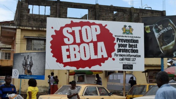 People walk past a billboard with a message about ebola in Freetown