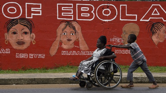 A boy in Monrovia pushes a woman in a wheelchair past a wall bearing information about Ebola in September. Some villages lost their entire working-age populations, leaving countless orphans behind in their place. One nonprofit that works with orphans believes that more than 12,000 children have lost their primary caregiver. Schools were shut down for almost a year and only recently reopened.