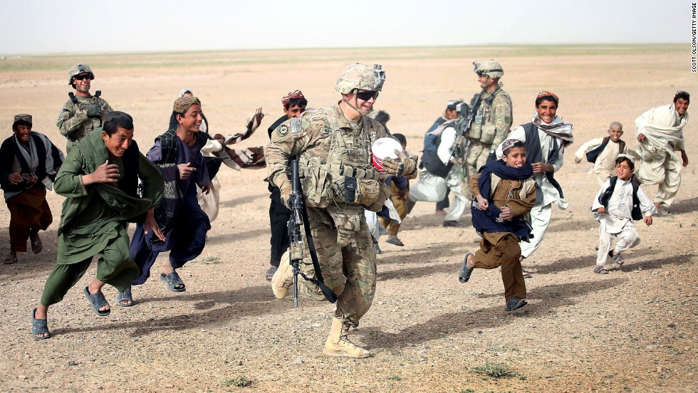 <strong>March 9: </strong>U.S. Army Spc. Taylor Burcham runs with a soccer ball that he gave to children near Kandahar, Afghanistan.