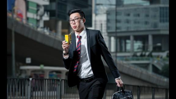A man sips a boxed drink in Hong Kong.