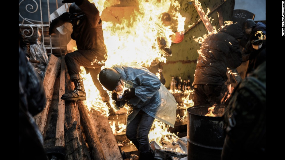 "Protesters in Kiev, Ukraine, catch fire as they stand behind burning barricades during clashes with police on February 20, 2014. Kiev's Independence Square had been the center of <a href=""http://www.cnn.com/2014/02/19/world/gallery/ukraine-protests-0218/index.html"">anti-government protests</a> since November 2013, when President Viktor Yanukovych reversed a decision on a trade deal with the European Union and instead turned toward Russia."