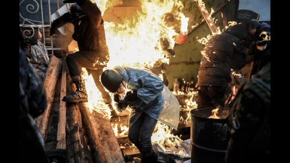 Protesters in Kiev, Ukraine, catch fire as they stand behind burning barricades during clashes with police on February 20, 2014. Kiev's Independence Square had been the center of anti-government protests since November 2013, when President Viktor Yanukovych reversed a decision on a trade deal with the European Union and instead turned toward Russia.