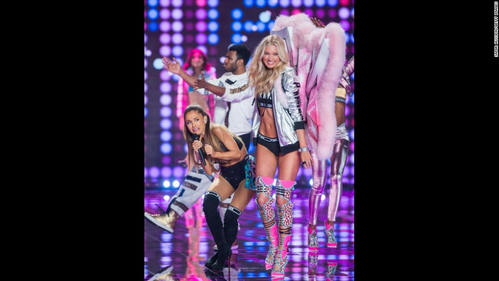 Pop star Ariana Grande sings on the runway as model Elsa Hosk walks past her at the Victoria's Secret fashion show Tuesday, December 2, in London.