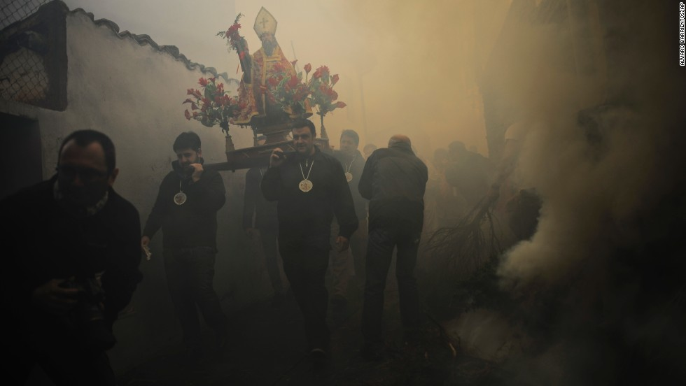 Devotees carry the relic of St. Andrews in the small town of Arnedillo, Spain, on Sunday, November 30. The smoke is part of their annual blessing.