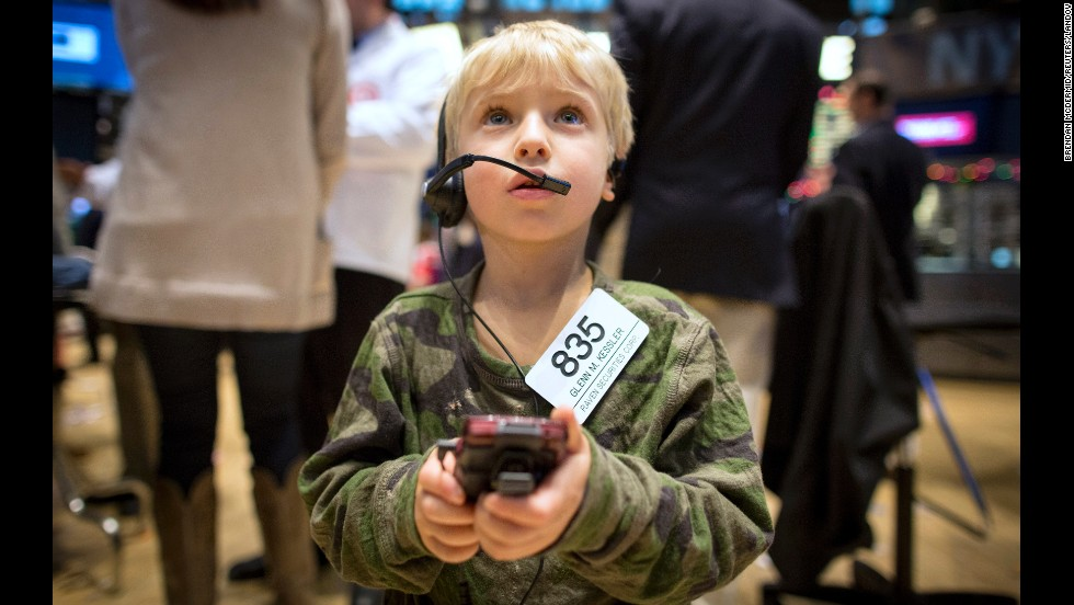 Jordan Kessler, son of trader Glenn Kessler, uses his father's cell phone and badge on the floor of the New York Stock Exchange on Friday, November 28. Traders traditionally bring their children to work for the half day of trading that takes place after the Thanksgiving holiday.