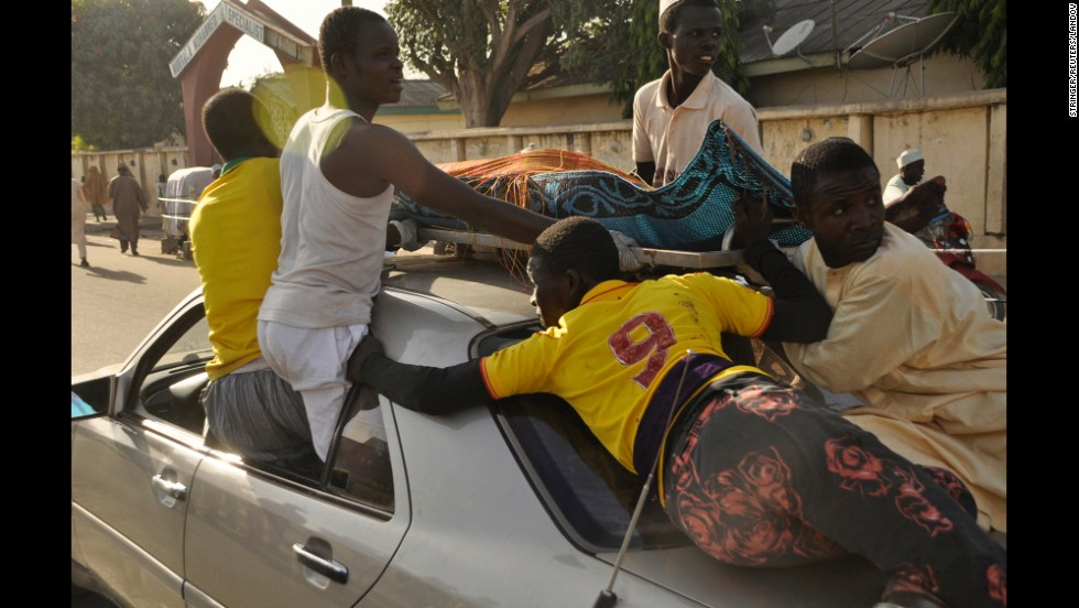 "A victim of a mosque bombing in Kano, Nigeria, is carried on top of a car before being buried on Friday, November 28. <a href=""http://www.cnn.com/2014/11/28/world/africa/nigeria-violence/index.html"">At least 120 people were killed and 270 others wounded</a> when two suicide bombers blew themselves up and gunmen opened fire on the congregation, a rescue official said."