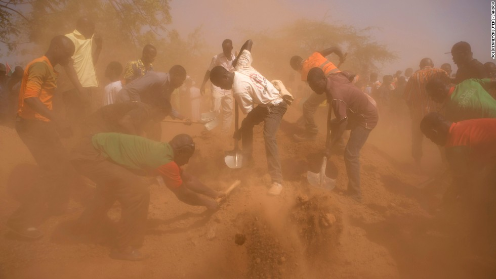 "During a funeral service Tuesday, December 2, in Ouagadougou, Burkina Faso, men bury the coffins of six people who were killed during <a href=""http://www.cnn.com/2014/10/30/world/africa/burkina-faso-unrest/index.html"">the country's uprising</a> in late October."
