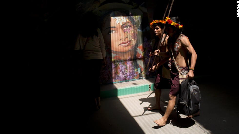 Men walk though a tunnel decorated with murals during the Climate Change Conference in Lima, Peru, on Monday, December 1. Delegates from more than 190 countries will meet in Lima for two weeks to work on a climate deal that is supposed to be adopted next year in Paris.