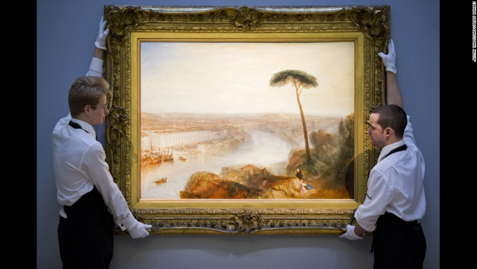 "Gallery assistants position a painting -- ""Rome, from Mount Aventine"" by British artist Joseph Mallord William Turner -- at Sotheby's auction house in London on Friday, November 28. The painting sold for $47.5 million."