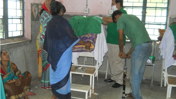 Medical staff use a bicycle pump to inflate a patient's abdomen during surgery.