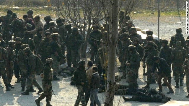 Indian soldiers gather around the bodies of suspected militants following an attack Friday on an army camp in Indian Kashmir.