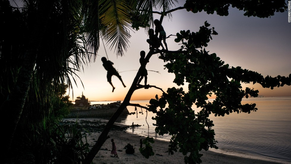 Children play on a swing. Kiribati's youth may be the last generation to live on these islands.