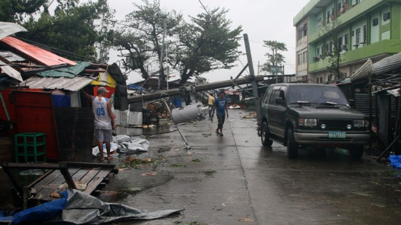 A man walks under a fallen utility pole in Tacloban, Philippines, on December 7.