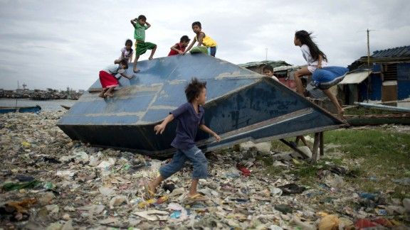 Children play on an overturned boat at the port area of Manila on Sunday, December 7.