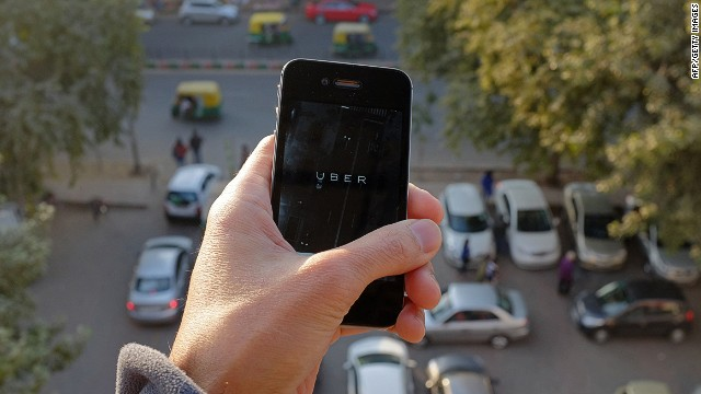 The Uber smartphone app, used to book taxis using its service, is pictured over a parking lot as auto-rickshaws (background) ply a road in the Indian capital New Delhi on December 7, 2014. An Uber taxi driver allegedly raped a 25-year-old passenger in the Indian capital before threatening to kill her, police said December 7, in a blow to the company's safety-conscious image. AFP PHOTO/TENGKU BAHARTENGKU BAHAR/AFP/Getty Images