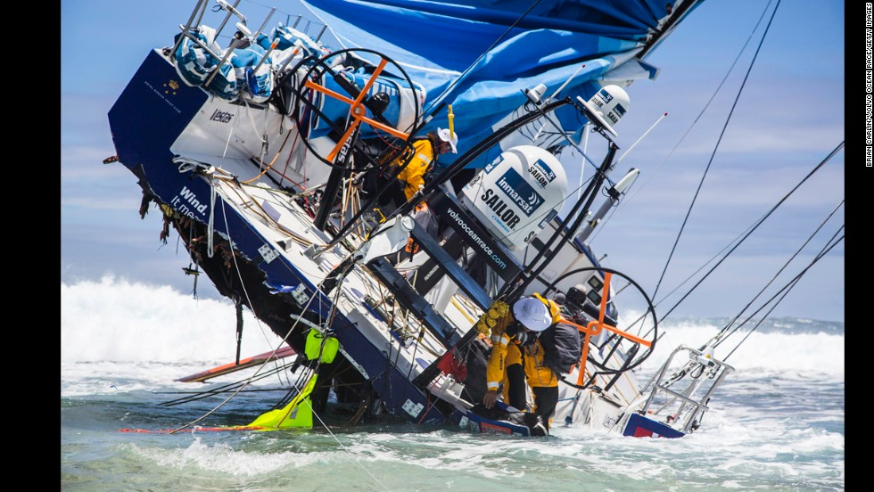 Crew members of Team Vestas Wind try to retrieve items from their boat after it hit a reef in the Indian Ocean during the Volvo Ocean Race on Wednesday, December 3. None of the crew was injured, but the boat was badly damaged.
