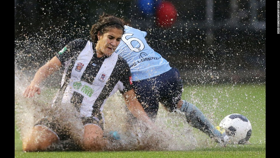 Water splashes in the air as Newcastle Jets player Angela Salem, left, slides on the turf during a W-League soccer match played Saturday, December 6, in Sydney.