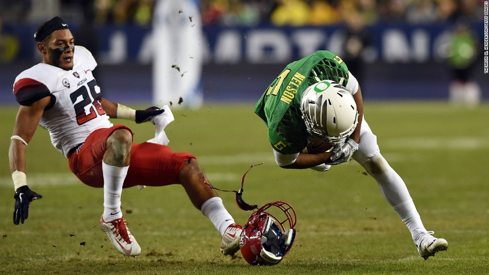 Arizona's Jourdon Grandon loses his helmet while defending Oregon's Charles Nelson during the Pac-12 Championship game Friday, December 5, in Santa Clara, California. Oregon won 51-13 to avenge its only loss of the season and solidify a spot in the College Football Playoff.