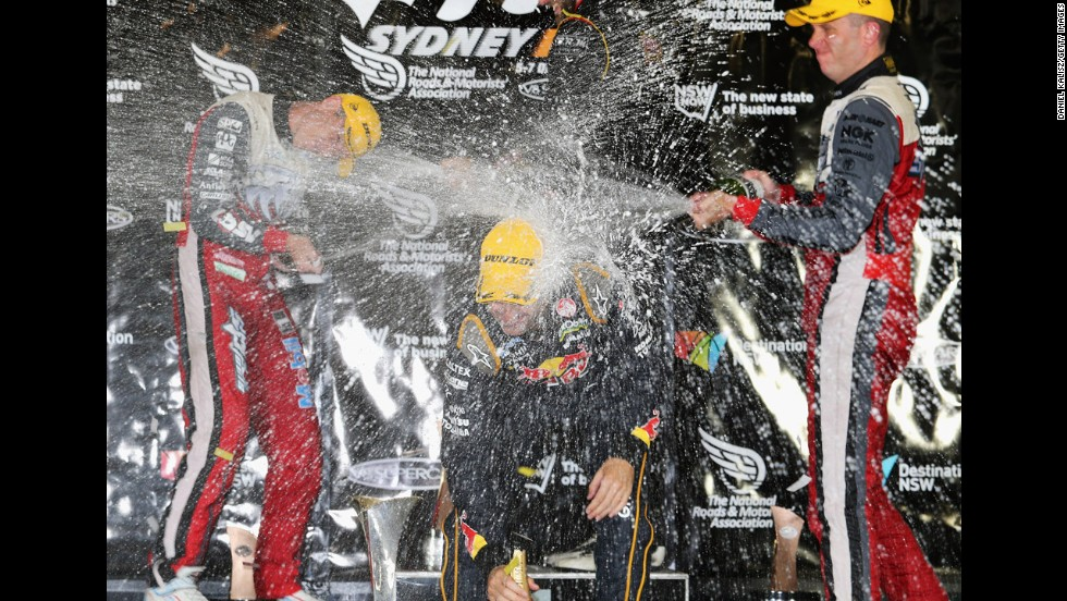 From left, V8 Supercar drivers James Courtney, Jamie Whincup and Garth Tander spray one another with champagne after a race at the Sydney 500 on Sunday, December 7.