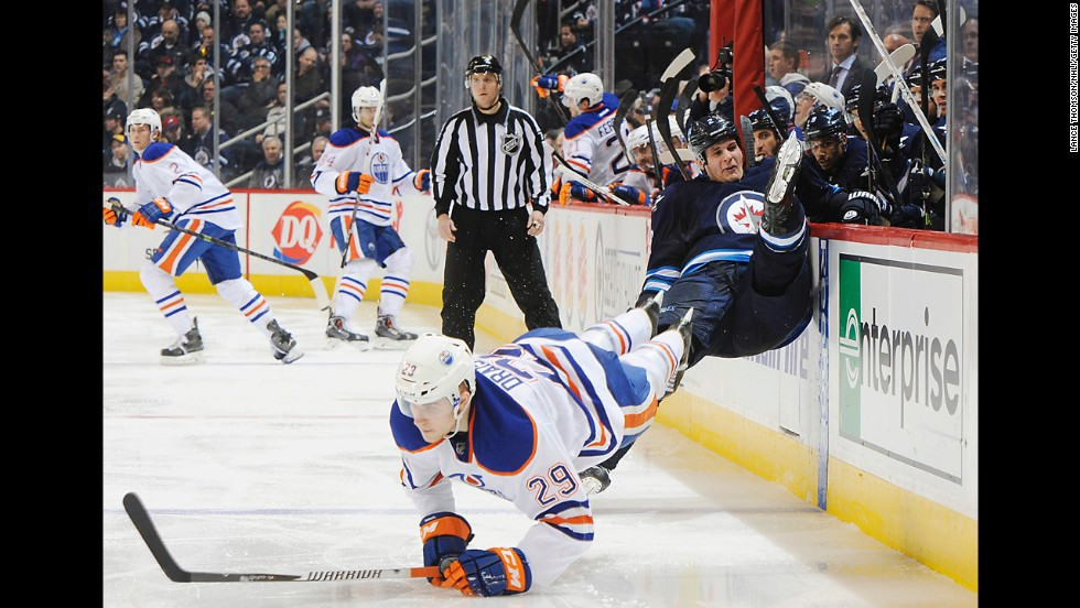 Edmonton's Leon Draisaitl and Winnipeg's Adam Pardy fall to the ice after colliding during an NHL game Wednesday, December 3, in Winnipeg, Manitoba.