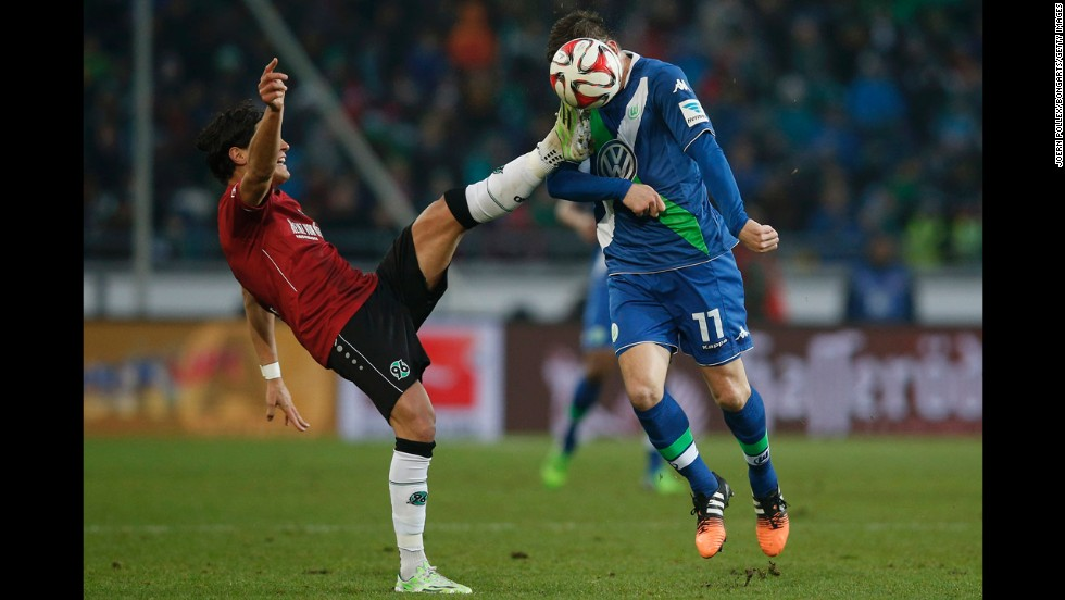 Hannover's Miiko Albornoz, left, and Wolfsburg's Ivica Olic compete for a ball during a Bundesliga match Saturday, December 6, in Hannover, Germany.