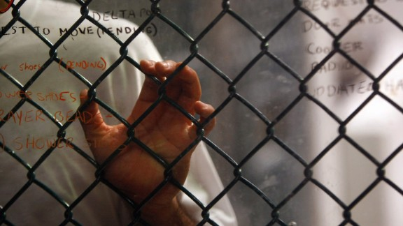 GUANTANAMO BAY, CUBA - OCTOBER 28: (EDITORS NOTE: Image has been reviewed by U.S. Military prior to transmission) A detainee stands at an interior fence at the U.S. military prison for