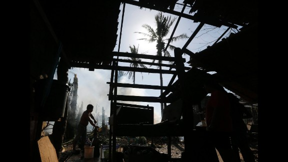 A man collects water near a damaged home in Dolores, Philippines, on Monday, December 8.