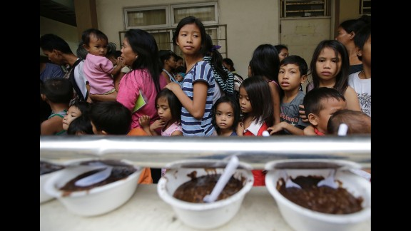 Evacuees line up for food at an evacuation center in Manila on December 8.
