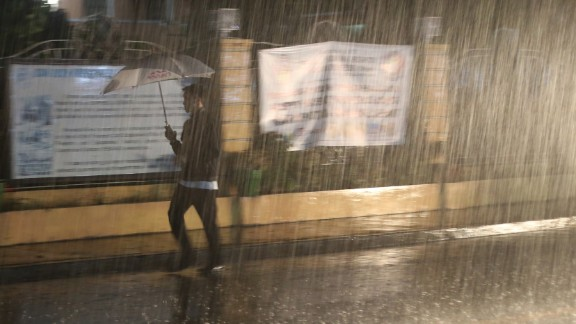 A man walks through heavy rain in San Juan, Philippines, on December 8.