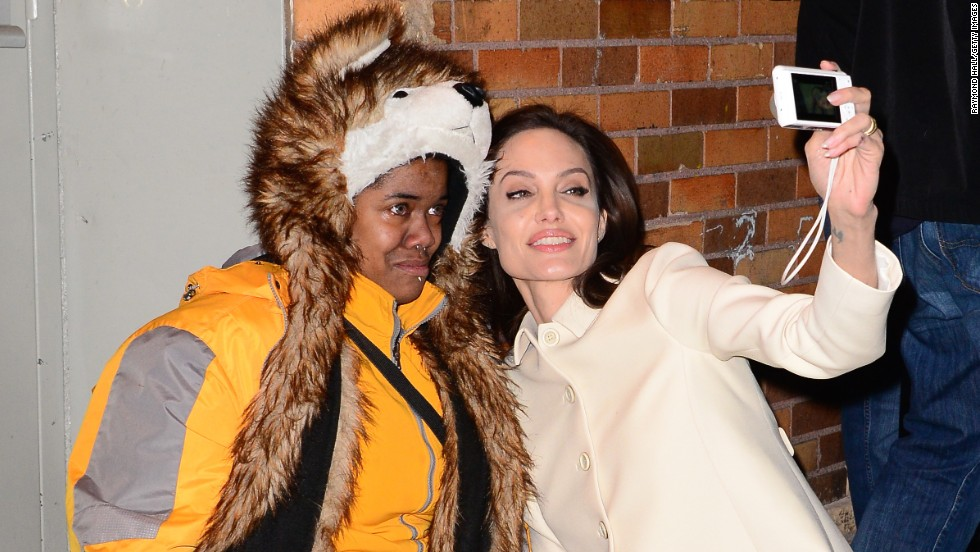 "Actress Angelina Jolie cheers up a crying fan with a selfie after appearing on ""The Daily Show"" in New York on Thursday, December 4. The fan <a href=""http://instagram.com/p/wNqIUyjFYM/"" target=""_blank"">said on Instagram</a> that she was having a panic attack when Jolie came to her aid."