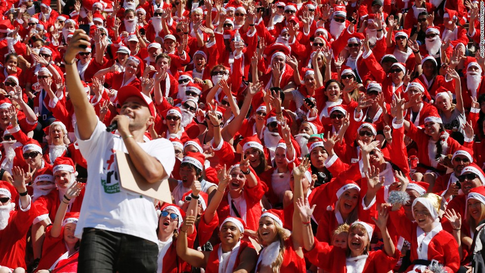 An announcer takes a selfie with people taking part in the annual Santa Fun Run in Sydney on Sunday, December 7.