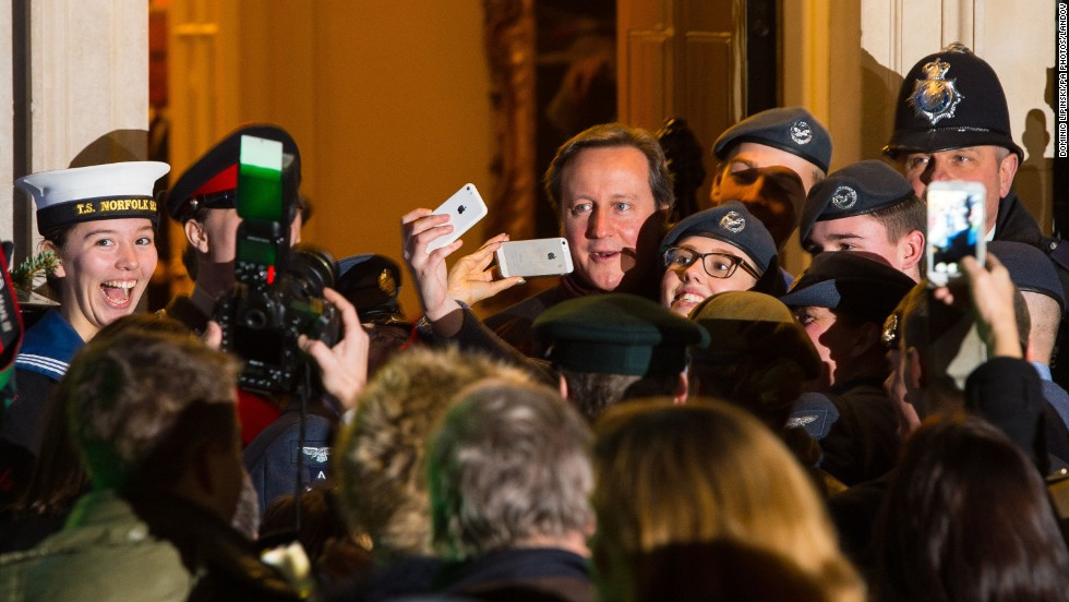 British Prime Minister David Cameron poses for a selfie with a group of air cadets at the switching-on of the Downing Street Christmas tree lights Monday, December 8, in London.