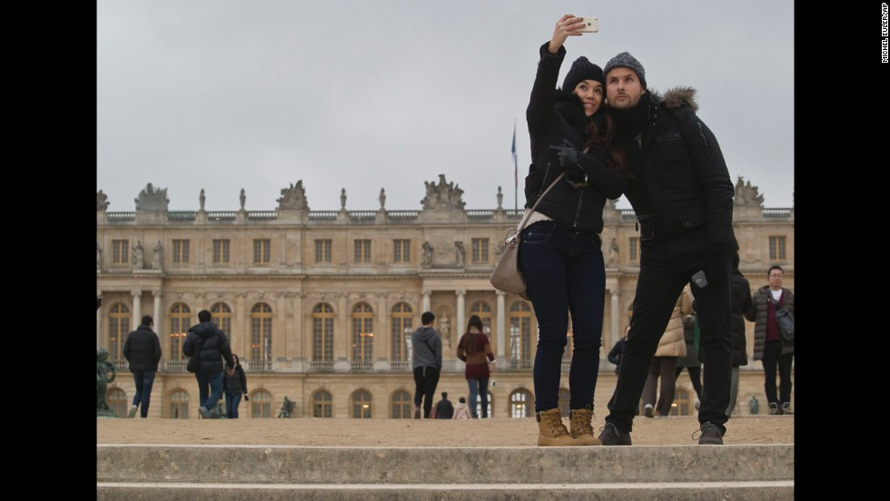 A couple in Versailles, France, takes a selfie in front of the Palace of Versailles on Friday, December 5.
