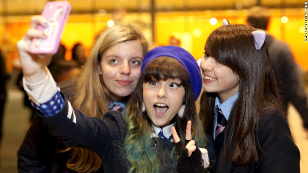 Singer Kelsey Ellison, center, snaps a selfie with fans after performing outside the YouTube office in central London on Wednesday, December 3.