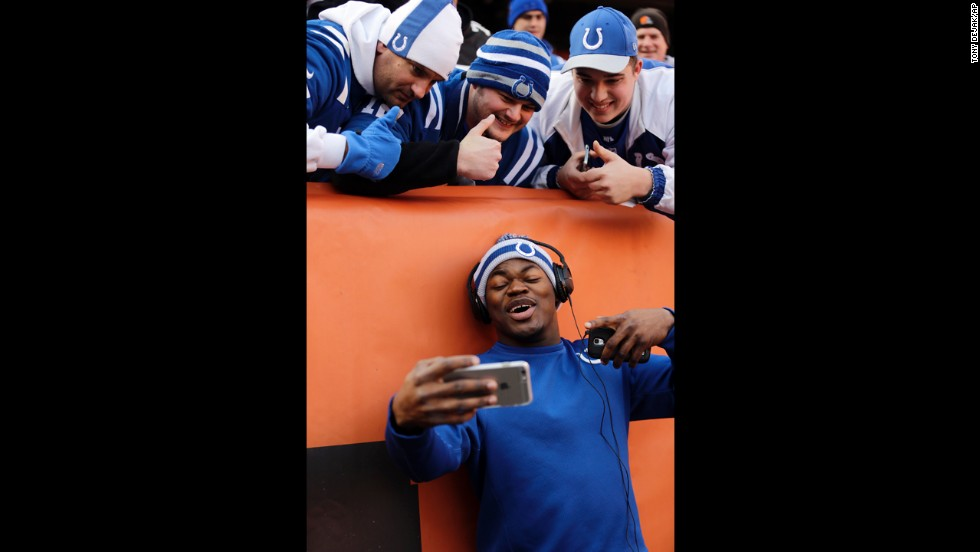 Indianapolis Colts linebacker Henoc Muamba takes a selfie with Colts fans before an NFL game in Cleveland on Sunday, December 7.