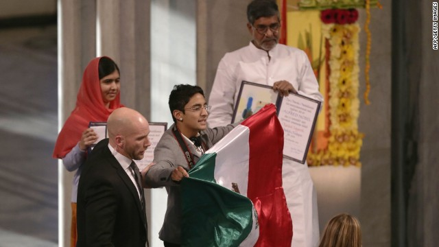A security staff blocks a man holding a Mexican flag on the stage next to Nobel Peace Prize laureates Malala Yousafzai (L) and Kailash Satyarthi (R) during the Nobel Peace Prize awarding ceremony at the City Hall in Oslo on December 10, 2014. The 17-year-old Pakistani girls' education activist Malala Yousafzai known as Malala shares the 2014 peace prize with the Indian campaigner Kailash Satyarthi, 60, who has fought for 35 years to free thousands of children from virtual slave labour.  AFP PHOTO / VEGARD WIVESTAD GROTTVEGARD WIVESTAD GROTT/AFP/Getty Images