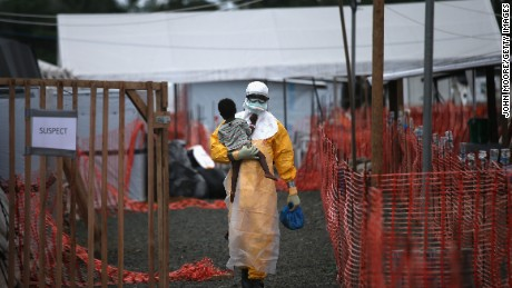 A Doctors Without Borders health worker in protective clothing carries a child suspected of having Ebola in a treatment center in Liberia in October 2014.