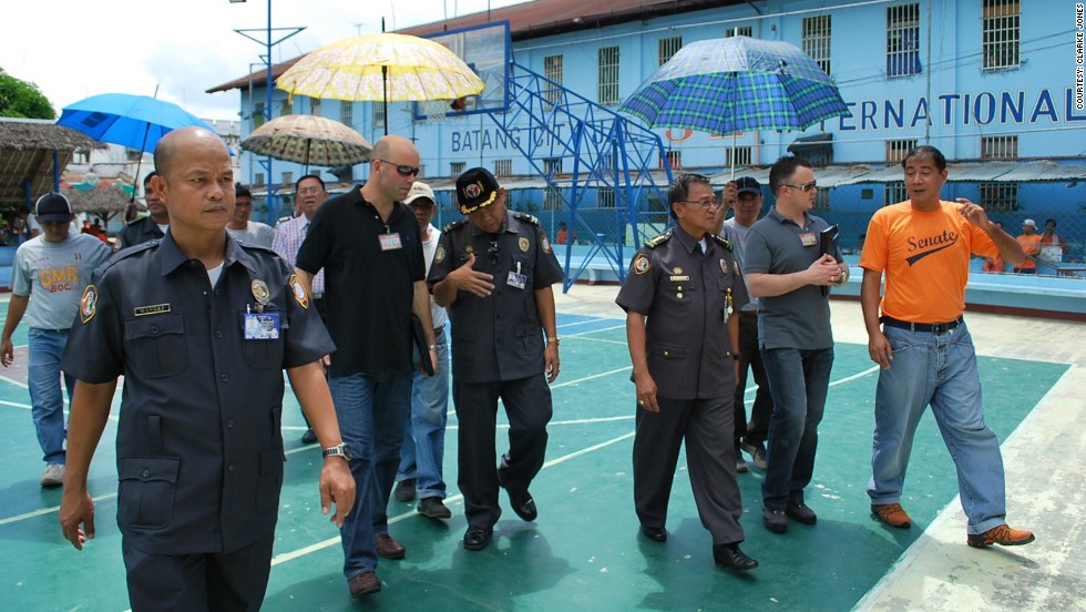 Prison researcher Clarke Jones walks across a basketball court at Batang City Jail, accompanied by a former senior prison superintendent, a correctional official from Australia and other guards.