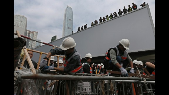 Workers clear barricades on December 11. Protesters wanted to pressure the government to allow open elections for Hong Kong