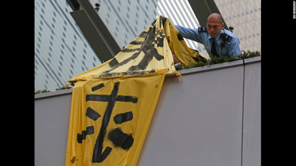 A police officer removes a protest banner from a bridge December 11.