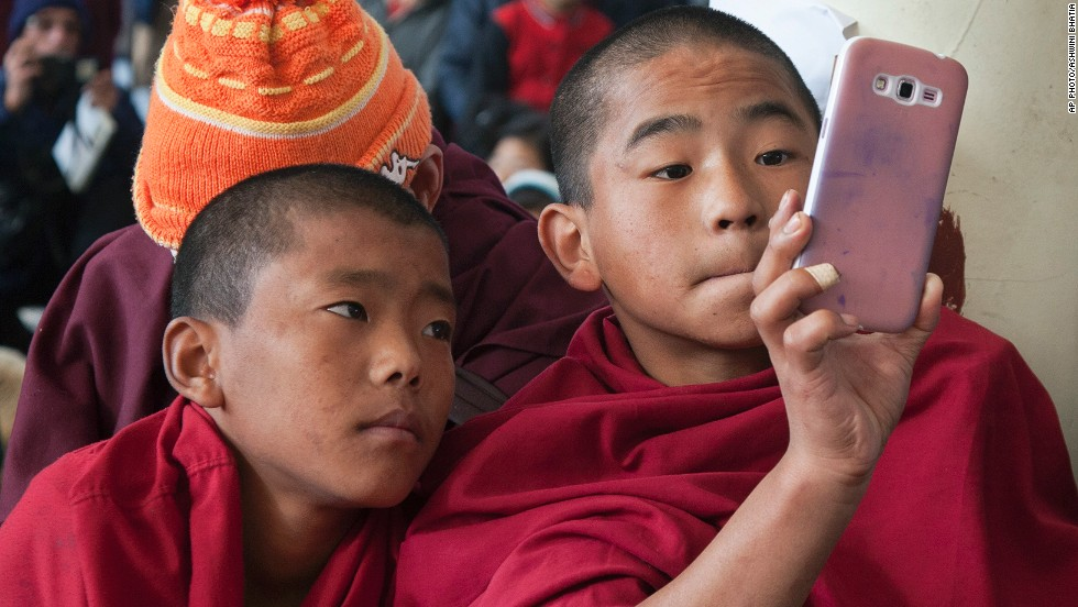 DECEMBER 11 - DHARAMSALA, INDIA: A novice exiled Tibetan Buddhist monk uses his mobile phone camera as people gather at the Tsuglakhang temple to mark the 25th anniversary of their spiritual leader, the Dalai Lama, receiving the Nobel Peace Prize. The Tibetan leader was awarded the prize in 1989 for his commitment to non-violence.