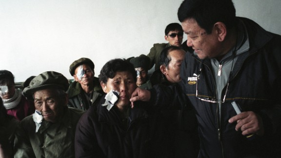 Kim Chun Son, 48, is overcome with emotion when Nepalese doctor Sanduk Ruit takes off her eye patch during a post operative examination in North Korea in 2005.