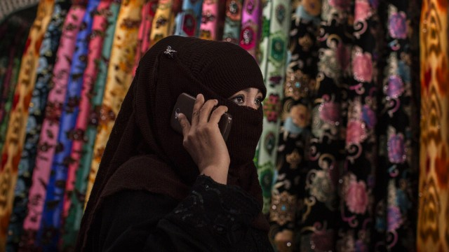 A Uyghur woman wears a veil as she shops at a local market on August 2, 2014 in Kashgar, Xinjiang Uyghur Autonomous Region, China.