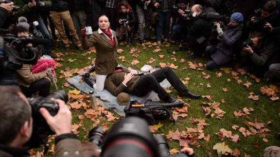 """Demonstrators take part in a mass """"face-sitting protest"""" outside the Houses of Parliament in central London."""