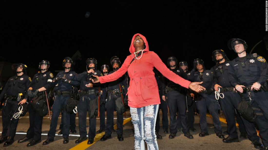Mikela Mosley speaks out in front of a line of police during a demonstration on Saturday, December 13, in Oakland, California.