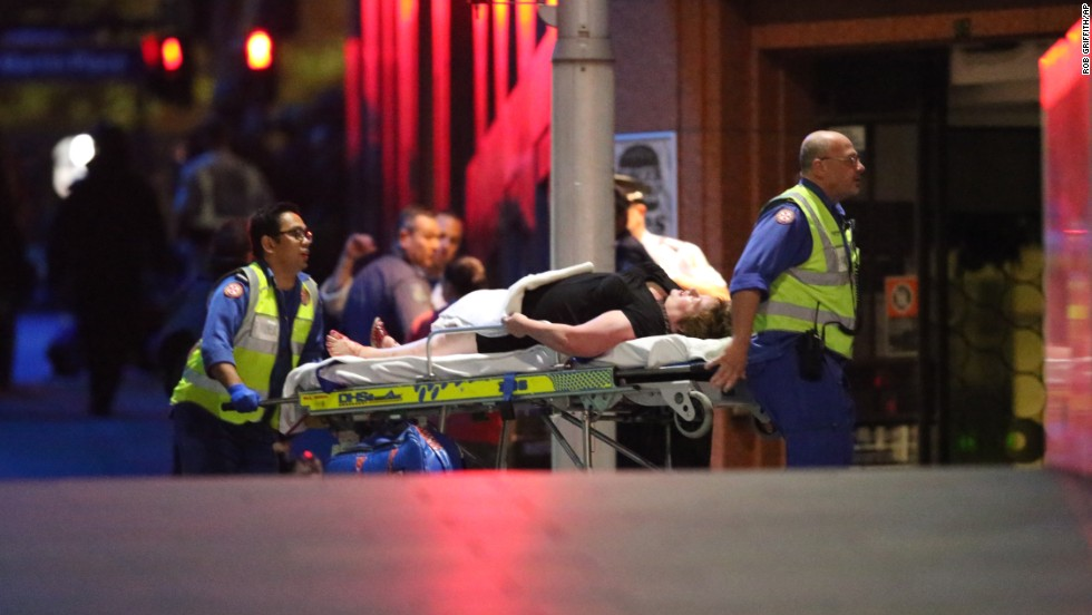 An injured hostage is wheeled to an ambulance after shots were fired during the raid on the cafe.
